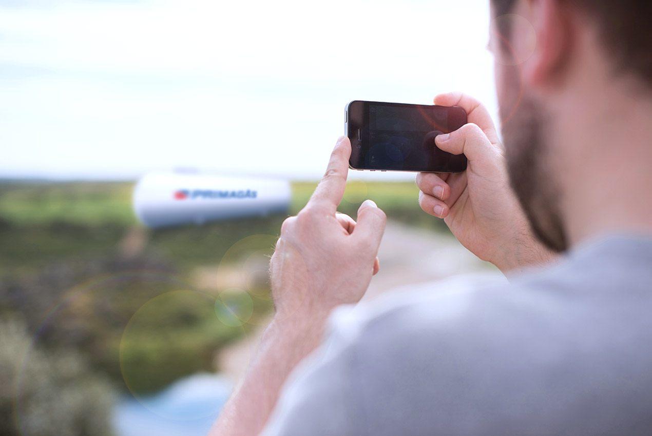 PRIMAGAS Fotodokumentation, Mann mit Handy fotografiert einen Flüssiggas-Tank