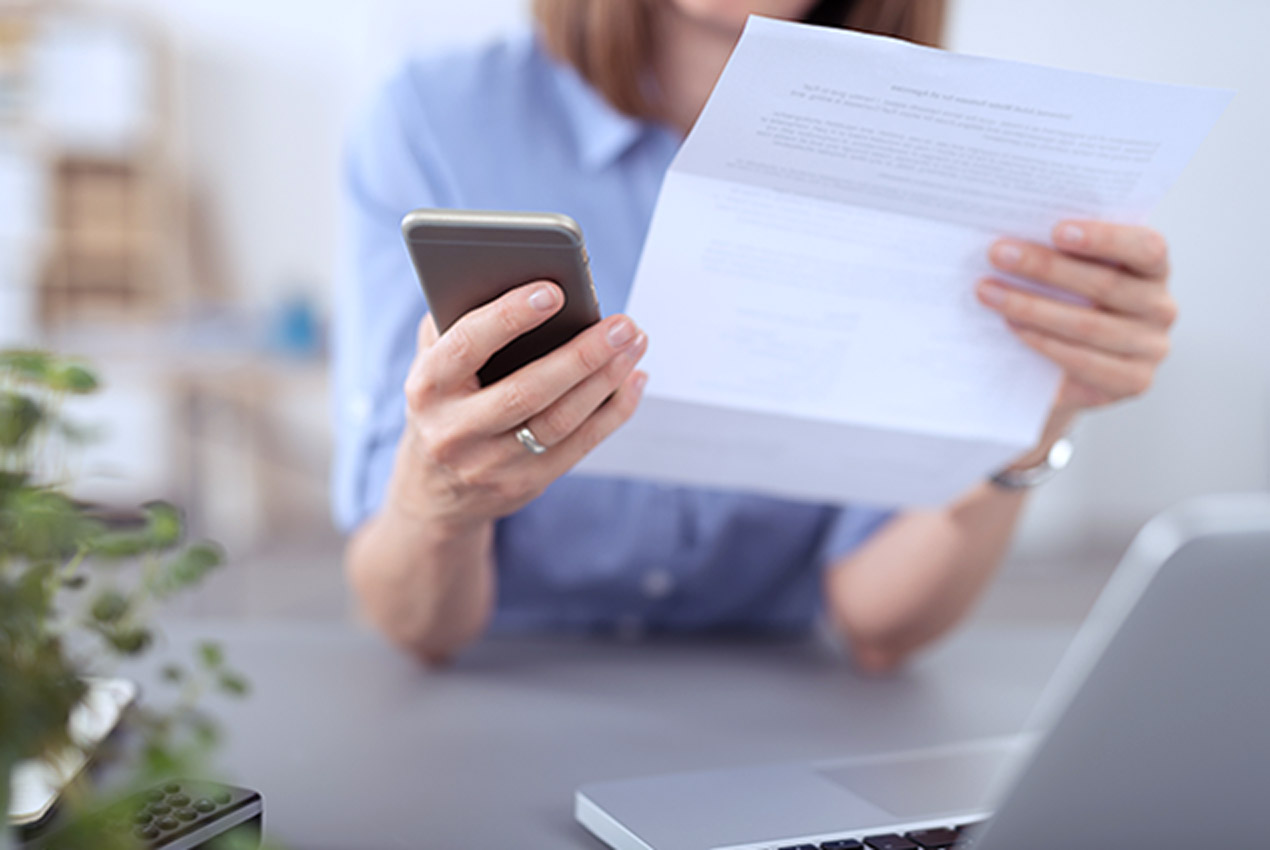 PRIMAGAS Abrechnung, Frau hält Rechnung und Handy in den Händen